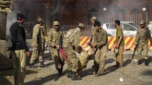 Soldiers move the body of a dead colleague from the site of the Mingora attack