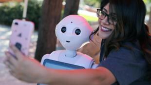 Una estudiante se toma una foto con 'Pepper', un proyecto humanoide de Inteligencia Artificial, en San Marcos, California.