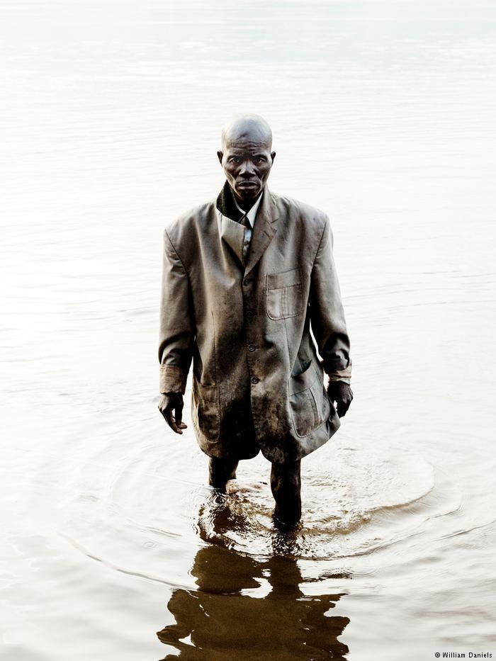 Un Centrafricain en veste, les pieds dans l'eau, cliché du photographe français William Daniels extrait du livre « RCA »