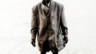 Un Centrafricain en veston, les pieds dans l'eau, cliché du photographe français William Daniels extrait du livre « RCA »