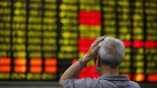 Shanghai. Devant le tableau du 16 juin, un homme assiste à la chute de la Bourse, au plus bas niveau depuis trois semaines.