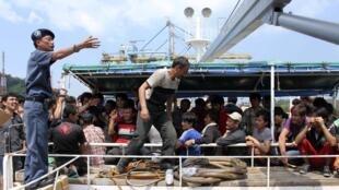 Un officier indonésien négocie avec les demandeurs d'asile afghans, iraniens  et irakiens pour qu'ils quittent leur embarcation.
