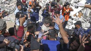 Palestinos sacan a una niña entre los escombros de un edifico bombardeado por Israel en Gaza, el 16 de mayo de 2021