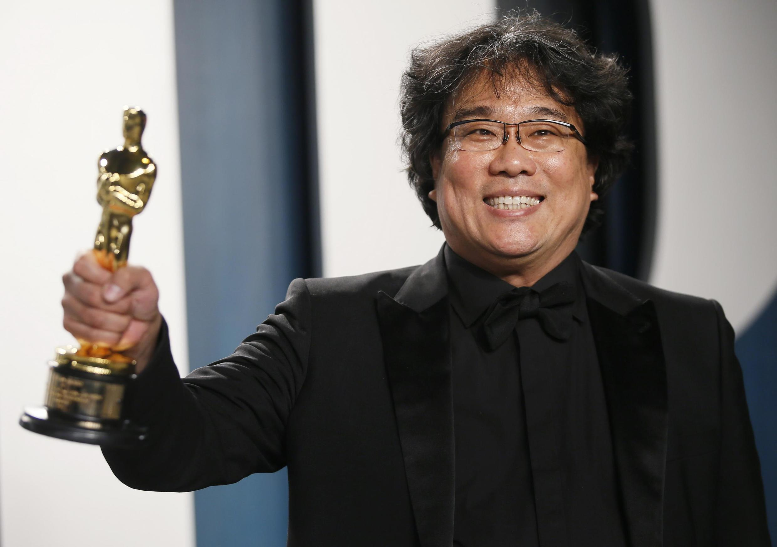 """Bong Joon Ho holds one of his Oscars for """"Parasite"""" at the Vanity Fair Oscar party in Beverly Hills during the 92nd Academy Awards, in Los Angeles, California, U.S., February 9, 2020."""
