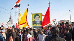 伊拉克反政府示威者2019年11月1日高举最高宗教精神领袖画像游行。
