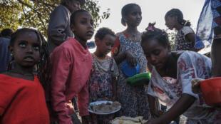 Niños desplazados en el oeste de Tigré, Etiopía, se reúnen para recibir un plato de alimentos.