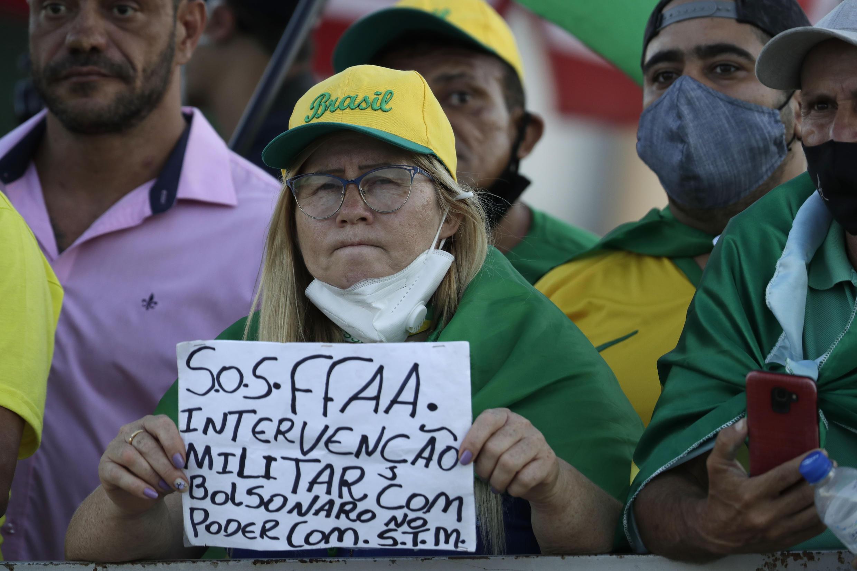 """Um manifestante segura uma placa em português que diz """"Forças Armadas SOS. Intervenção militar com Bolsonaro no poder"""" durante uma manifestação em apoio ao presidente brasileiro Jair Bolsonaro em frente ao palácio presidencial do Planalto em Brasília, Brasil, na segunda-feira, 29 de março de 2021."""