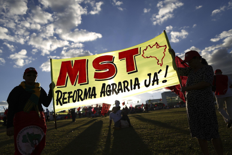 Des manifestants brandissent une bannière appelant à la réforme agraire immédiate, lors de la journée de grève nationale au Brésil, jeudi 11 juillet.
