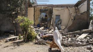 Una mujer pasa frente a una vivienda dañada por las bombas cuando las fuerzas federales entraron en la ciudad de Wukro, en la región de Tigré, el 1 de marzo de 2021 al norte de Etiopía