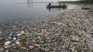 Dans la baie de Manille, les pêcheurs préparent leurs filets, en juin 2013, sur une plage jonchée de déchets plastiques.