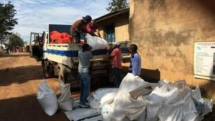 Workers lift sacks of rice, beans, and salt for a WFP food distribution for Ebola survivors in Beni, North Kivu, DRC
