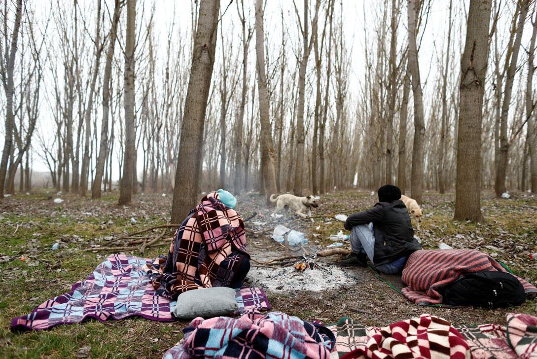 Des migrants sont assis dans un champ à la frontière turco-grecque dans le village de Doyran près d'Edirne, en Turquie, le 4 mars 2020.