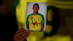 A fan holds up a picture of missing Argentine footballer Emiliano Sala at a vigil in the French city of Nantes, 22 January 2019.