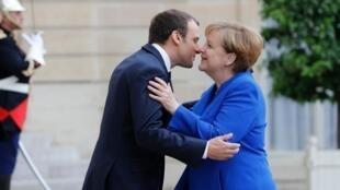 El presidente francés Emmanuel Macron y Angela Merkel se saludaron con un beso en el Palacio del Elíseo, París, el 13 de junio de 2017.