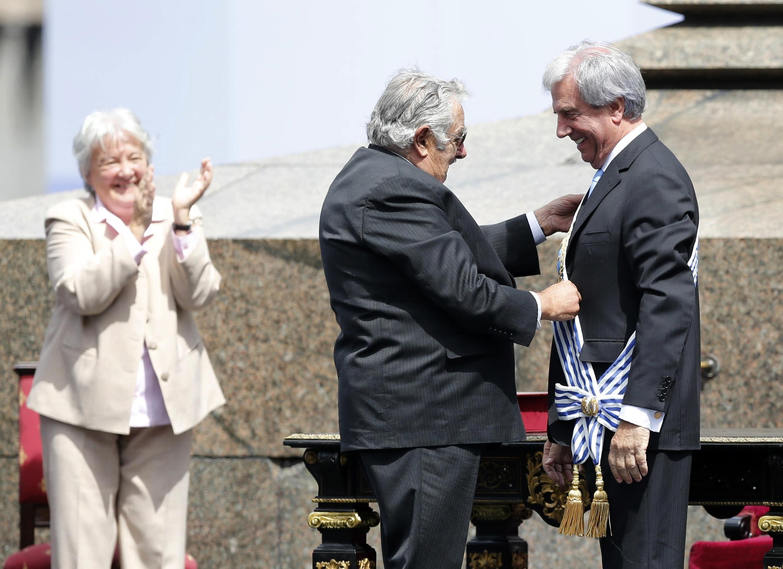 El presidente saliente, José Mujica (izquierda), coloca la banda insignia del mando al presidente electo, Tabaré Vásquez, Montevideo, 1° de marzo de 2015.