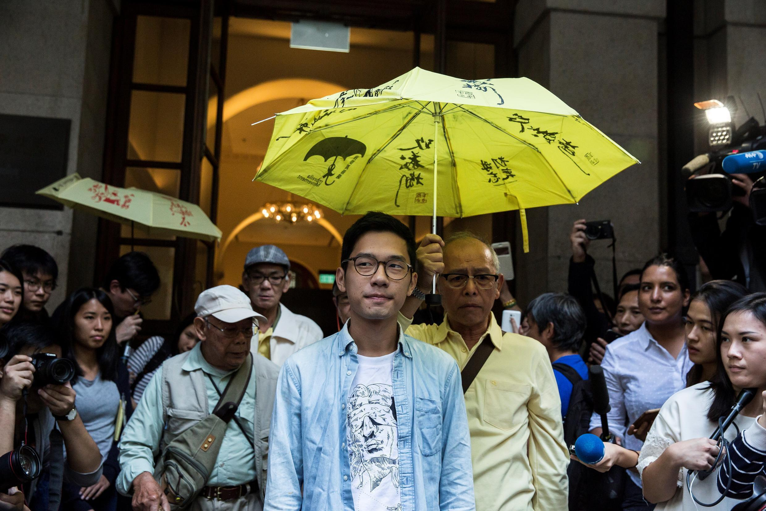 Pro-democracy activist Nathan Law (C) says he has relocated to Britain after fleeing Hong Kong because of a tough new security law imposed by Beijing