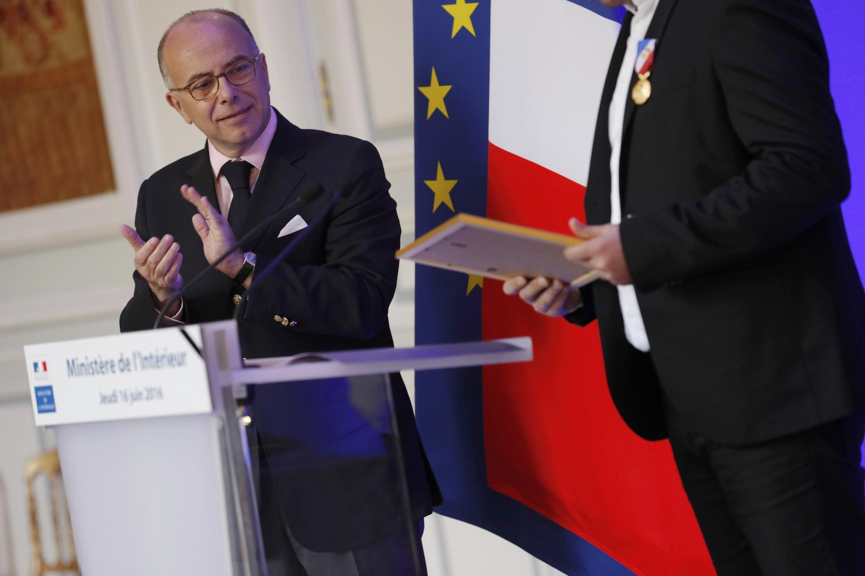 Глава МВД Франции Бернар Казнев (слева) аплодирует охраннику Bataclan на церемонии при вручении ему гражданства, Париж, 17 июня 2016 г.