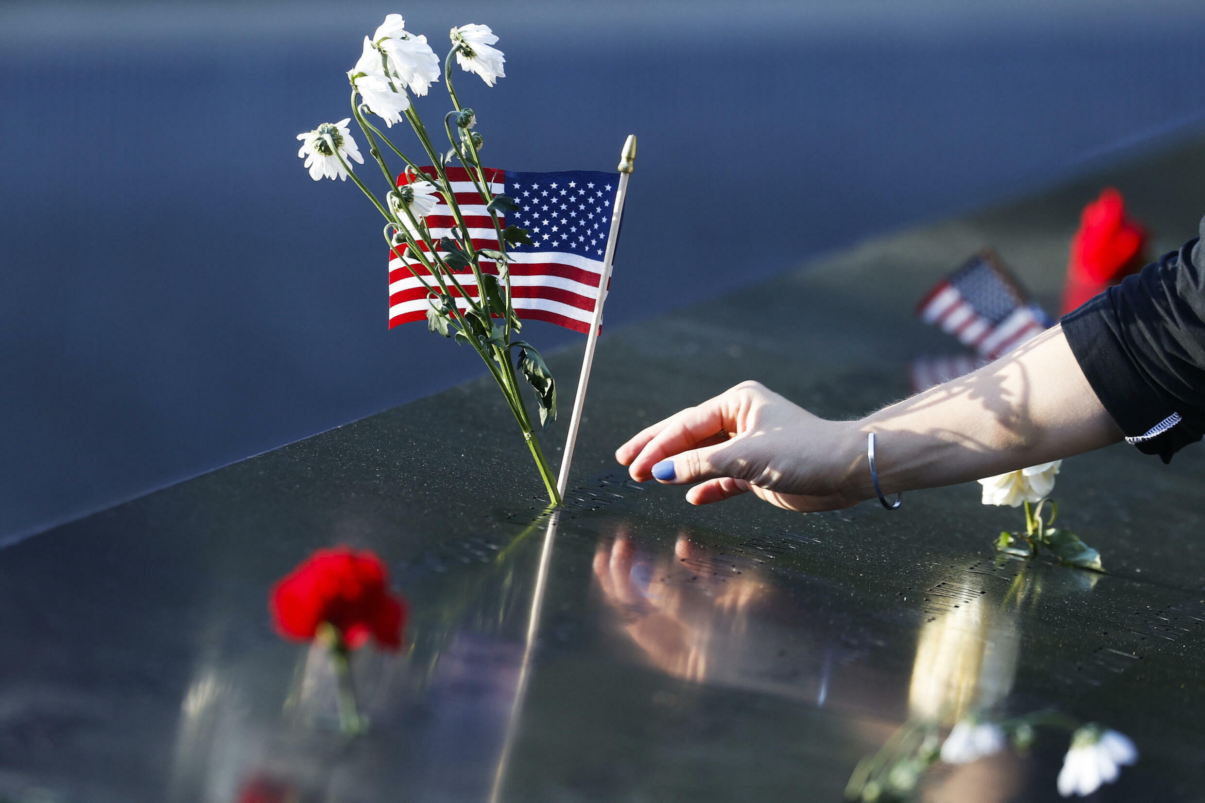 A person places flowers and a U.S. flag on a name inscribed on the National September 11 Memorial on the 20th anniversary of the terrorist attacks in New York, Saturday, Sept. 11, 2021.
