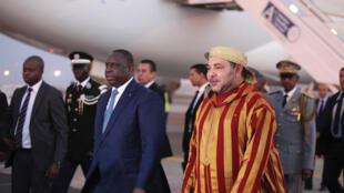 Le roi du Maroc, Mohammed VI, accueilli par le président sénégalais, Macky Sall, lors de son arrivée à Dakar, le 20 mai 2015.