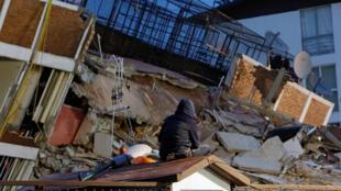 Une personne est assise sur le toit d'une petite maison en regardant les décombres d'un bâtiment effondré après un tremblement de terre qui a frappé Mexico au Mexique, le 20 septembre 2017.