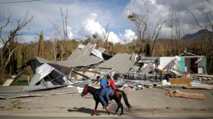 Residentes de Puerto Rico montan a caballo frente a un casa destruida por el Huracán María en Jayuya, el 4 de octubre de 2017.