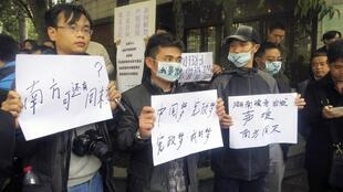 Demonstrators hold banners outside the headquarters of Southern Weekly newspaper in Guangzhou, Guangdong province