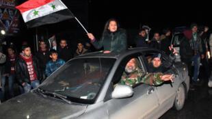 Des Syriens dans les rues d'Alep jeudi 22 décembre pour célébrer la reprise en main de la ville pour le régime Assad.