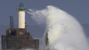 Waves crash against a lighthouse as the wind blows at around 100 km in Boulogne-sur-Mer, northern France on 7 February, 2016.