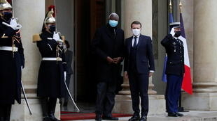 French President Emmanuel Macron and Interim Malian President Bah Ndaw wave to journalists as they enter the Elysee Palace in Paris, France, January 27, 2021.