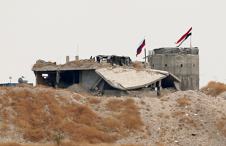 Российский и сирийский флаги на входе в селение Зор Магар, на северо-востоке Сирии, 23 октября 2019.