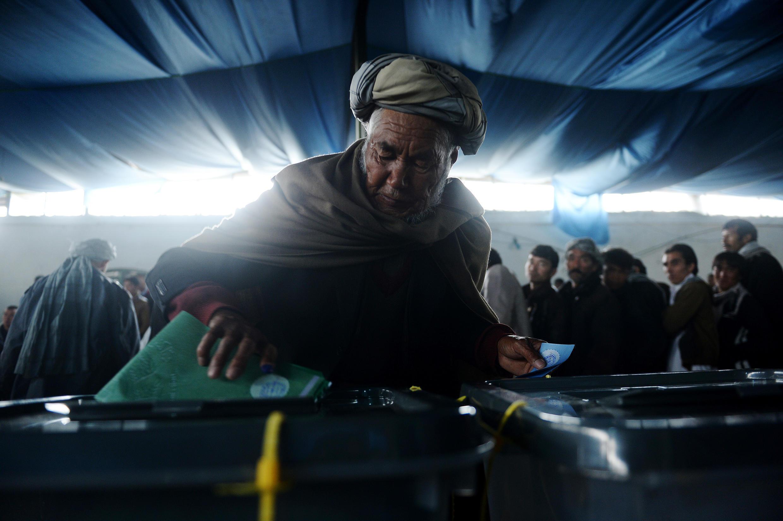 Eleitor deposita voto em urna, na capital afegã, Cabul.