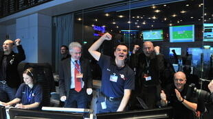 Mission controllers cheer the first signal received from the Rosetta spacecraft on 20 January 2014.