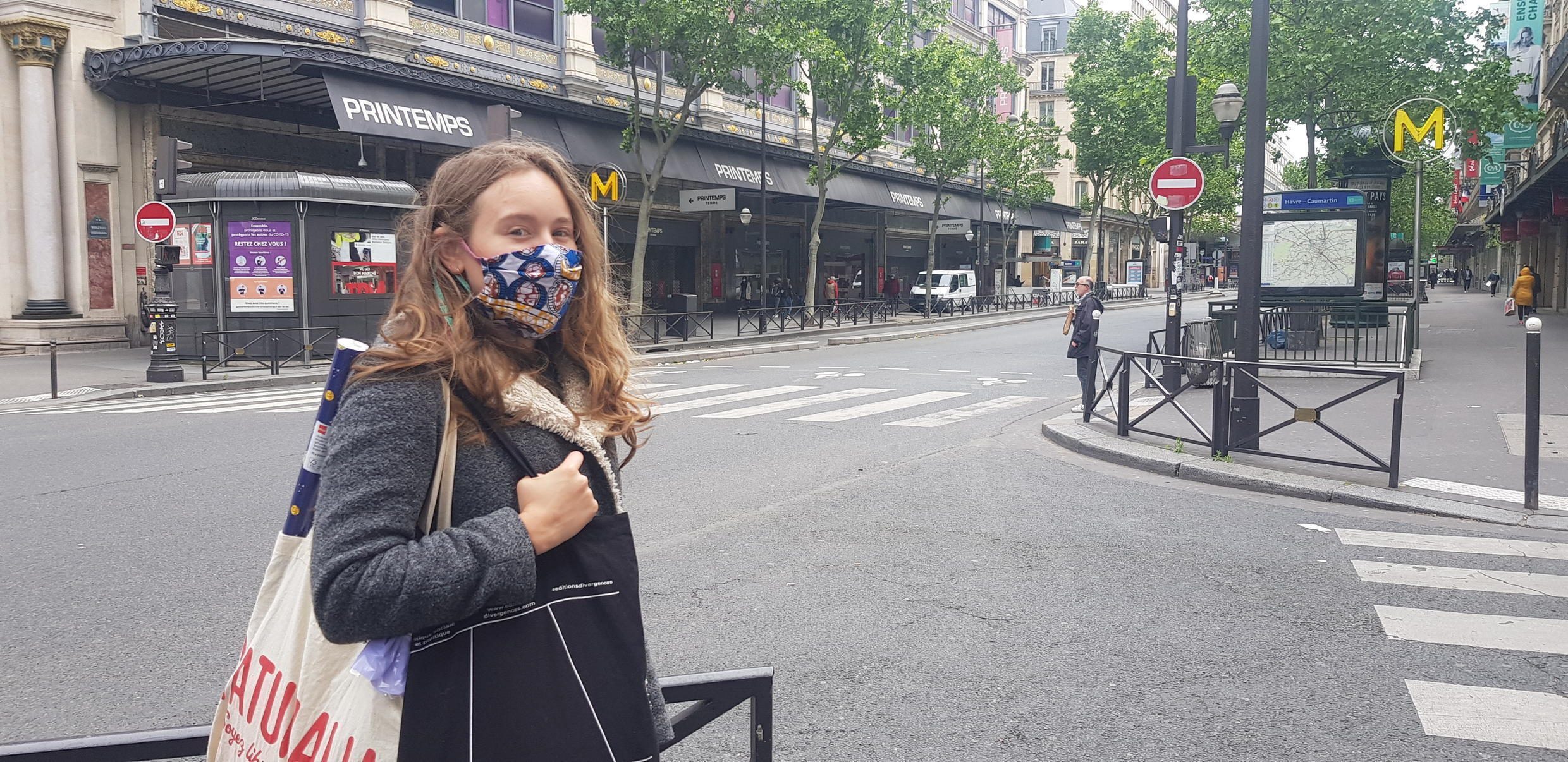 Zoé, in a handmade mask, is desperately looking for a birthday gift for her boyfriend as she scans the shops along a deserted Boulevard Haussmann.