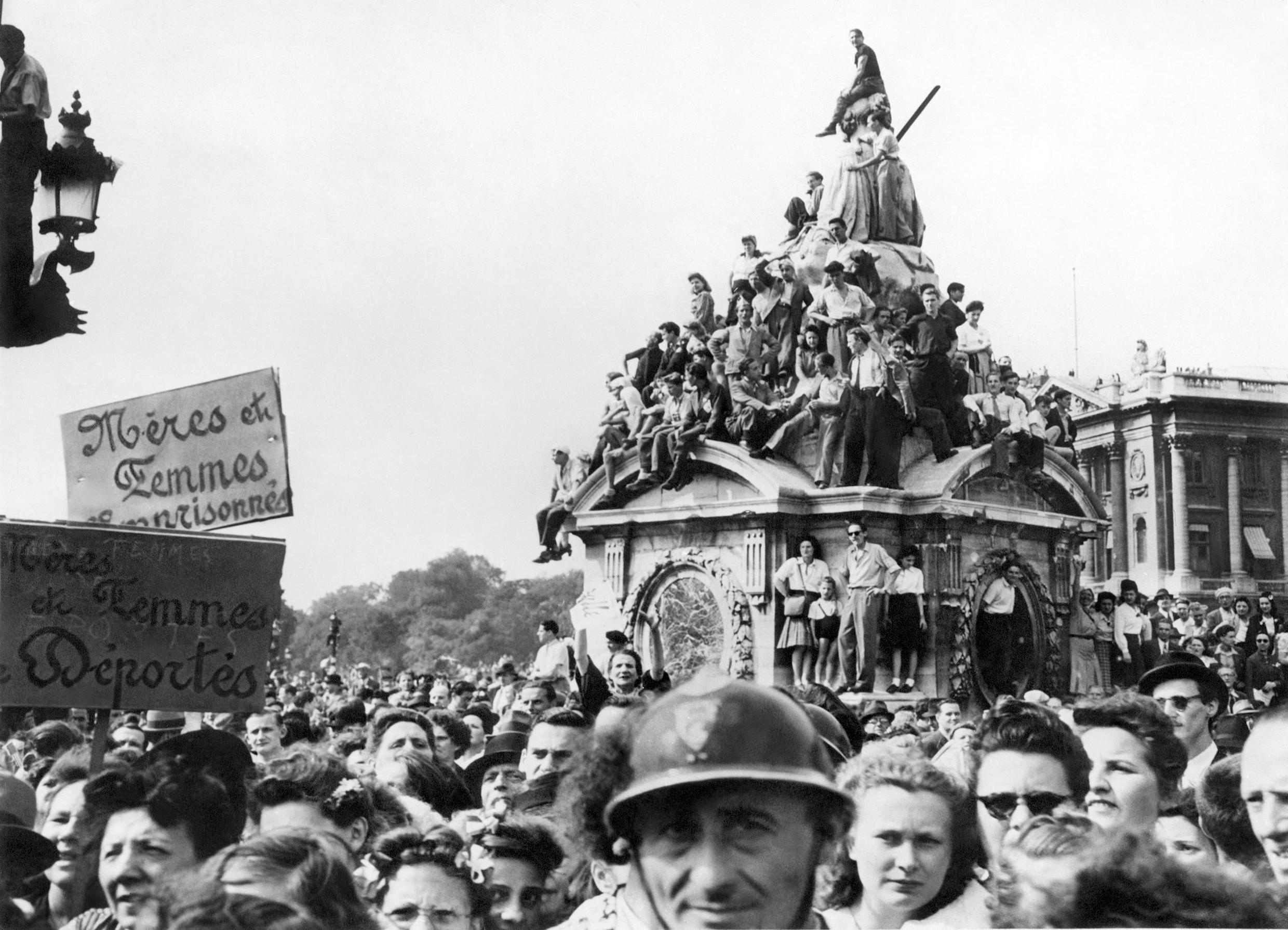 On August 26, 1944 Parisians cheer for General Charles De Gaulle, President of French Committee of Liberation, as he passes by Place Concorde at the head of the Victory Parade in Paris during the Liberation of the French capital.