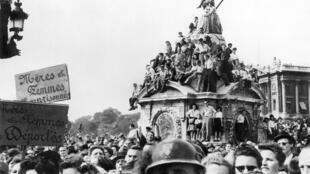 Parisienses comemoram liberação de Paris com passagem do General Charles De Gaulle pela Praça da Concórdia.