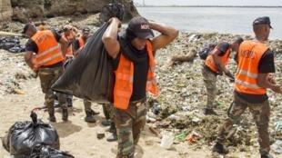 Empleados del Ministerio de Obras Públicas y Comunicaciones recogen residuos en las playa de Güibia, en Santo Domingo, el 16 de julio de 2018.