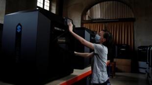 Un ingénieur travaille sur une des imprimantes 3D installées pour produire en masse du matériel médical à l'hôpital Cochin à Paris, le 3 avril 2020.