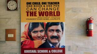 Cartaz da jovem Malala Yousafzai e do pai na parede da escola Khushal, região natal de Swat, no seu regresso do Reino Unido