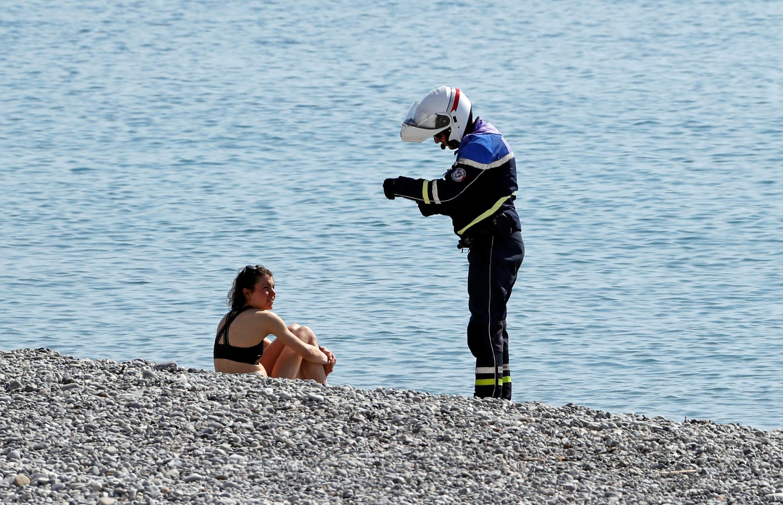 Policial adverte frequentadora da proibição de ir à praia.