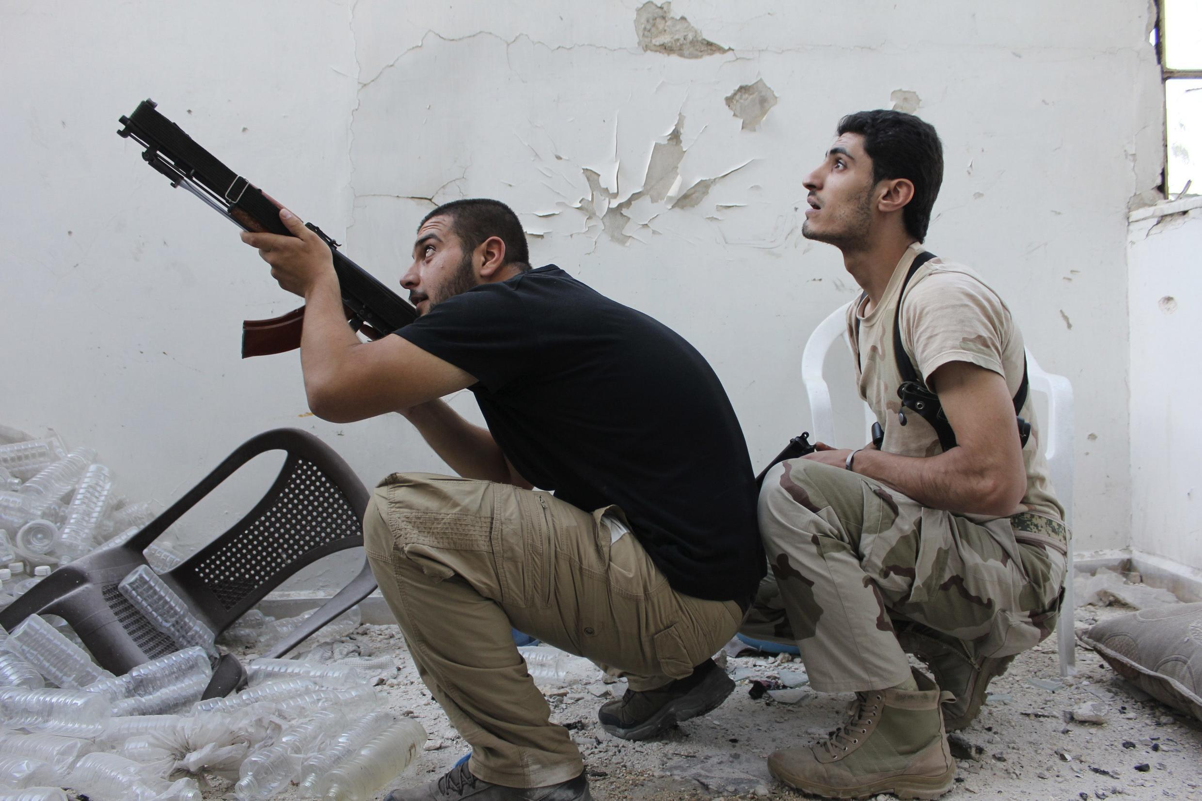 A Free Syrian Army fighter points his weapon as his fellow fighter watches in Aleppo's Al-Ezaa neighbourhood September 11, 2013.
