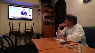 Restaurant owner watches Prime Minister announcing opening of cafés and restaurants on 28 May 2020.