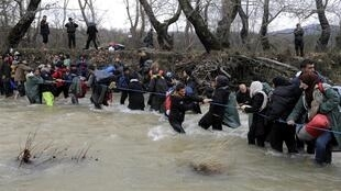 Migrants wade across a river near the Greek-Macedonian border, west of the the village of Idomeni, on 14 March, 2016.