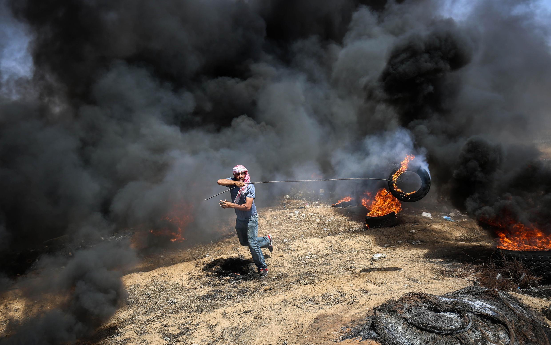 Des protestataires qui s'approchent de la barrière de séparation entre la bande de Gaza et Israël, tentant de se cacher derrière des écrans de fumée noire provoqués par des incendies de pneus, le 11 mai 2018.  .