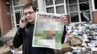 Une photo montrant le dessinateur Charb, qui présente une couverture de Charlie Hebdo, floutée par le NY Daily News