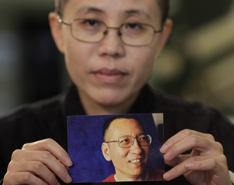Liu's wife Liu Xia holds up a picture of him