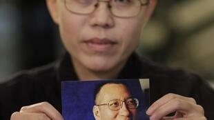 Liu's wife Liu Xia holds up a picture of him