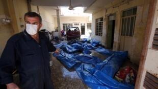 Un sauveteur irakien désigne les corps d'habitants du quartier d'Al Jadida à Mossoul, après des frappes aériennes contre le groupe Etat islamique.