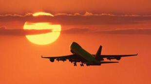 Un avión viaja en pleno atardecer.