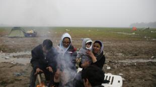 Des migrants afghans se réchauffent tant bien que mal, à la frontière entre la Grèce et la Macédoine, près du camp d'Idomeni, le 18 mars 2016.