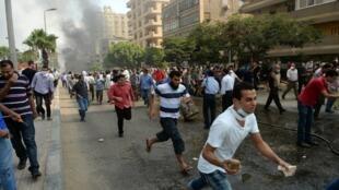 Manifestantes pró-Mursi fogem da polícia no Cairo nesta quarta-feira, 14 de agosto de 2013.